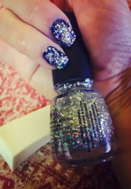 Glitter nails with the bottle of nail polish.