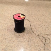 Pre-thread Your Needles - spool of black thread with a rethreaded needle stuck in the thread