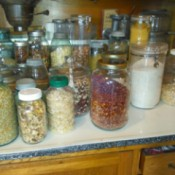 A counter filled with pickle jars with beans, rice or other dry goods stored in them.