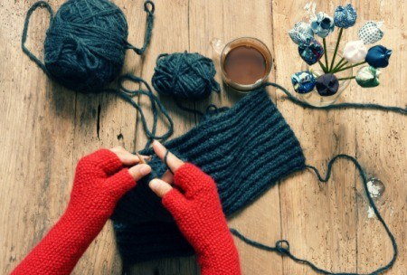 Hands wearing red fingerless knit  gloves knitting a scarf.