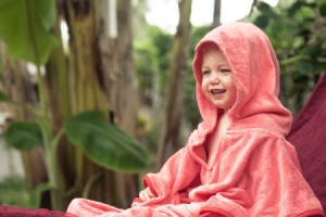 Happy Toddler wearing a pink hooded blanket outside.