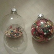 Two clear ornaments filled with beads.