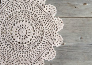 Beautiful intricate crochet doily on a grey wood background.