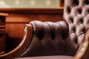Close up of a brown leather chairs arm.