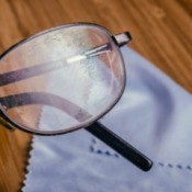 A pair of scratched eyeglasses on a cleaning cloth.
