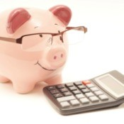 A pink piggy bank wearing glasses next to a calculator.