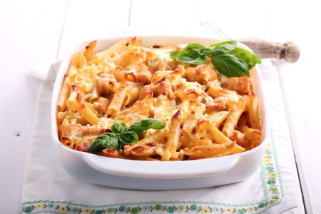 Baked Chicken Penne in a white dish with sprigs of fresh basil.