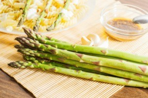 Asparagus in front of a penne dish and a sauce.