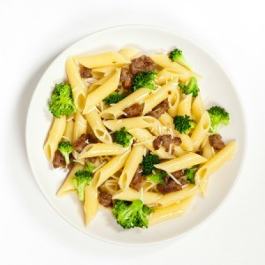 A plate of penne with sausage and broccoli.