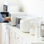 A white kitchen counter filled with small white appliances in a row.