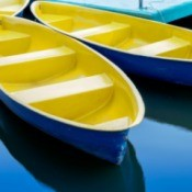 Two yellow and blue fiberglass rowboats.