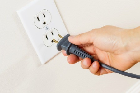 A hand ready to plug a cord into an electrical outlet.