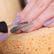 Woman applying silver glitter nail polish on ring finger.