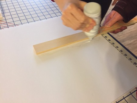 Gluing on the paint stirrer to the center back of the foam core.