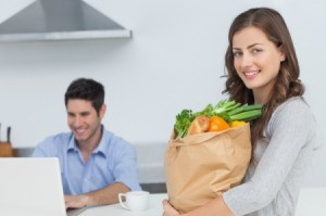 A couple with a computer and a bag of groceries.