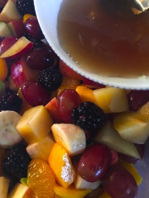 Fruit Salad with Maple Lime Dressing - pouring dressing on fruit