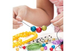 A girl making a beaded bracelet with colorful beads.