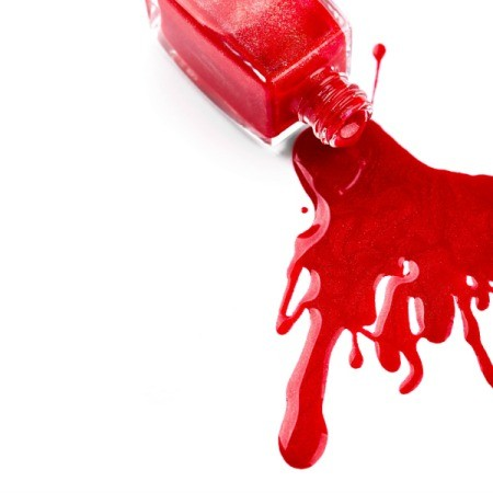 A bottle of nail polish spilled on a white background.