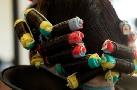 A woman in the middle of getting a perm at a salon.