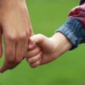 A child holding hands with a young adult.