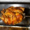 A chicken being cooked in a home rotisserie.