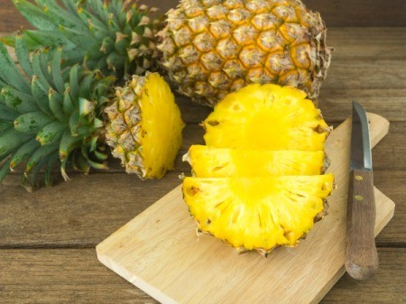 A fresh pineapple being chopped up for use in a recipe.