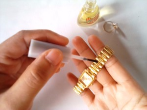Nail Polish for Shiny Jewelry - applying clear nail polish to a watchband