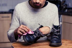 A man cleaning his leather work boots with a cloth.
