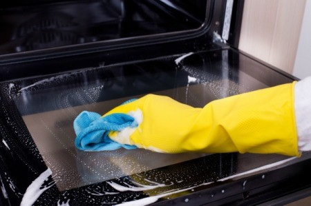 A person wearing rubber gloves, cleaning an oven.