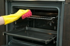 A rubber gloved hand cleaning oven racks with a pink sponge.