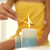 A woman lighting a candle.