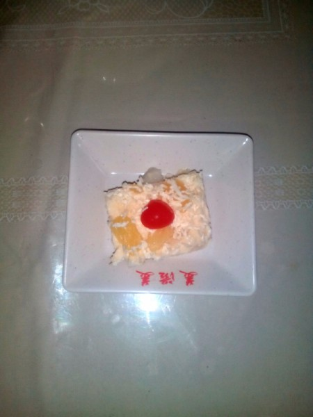 Cut piece of fruity pudding on plate.