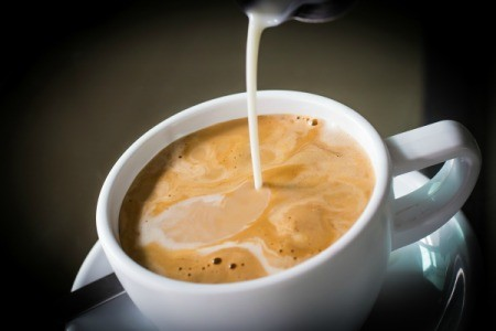 Pouring liquid coffee creamer into a cup of coffee.