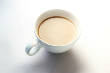 A cup of coffee with cream in it.