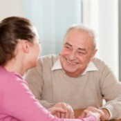 A woman sitting talking to an elderly man.