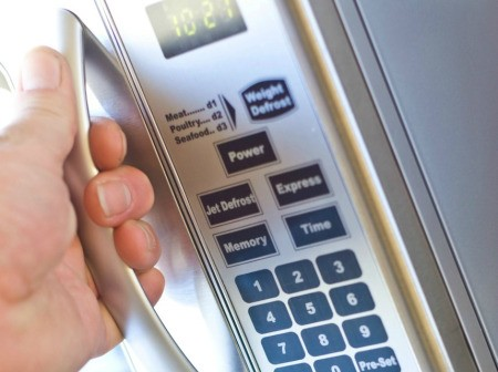A hand pulling the handle on a microwave oven.