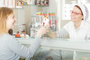 A woman working at an ice cream shop handing a cone to a customer.