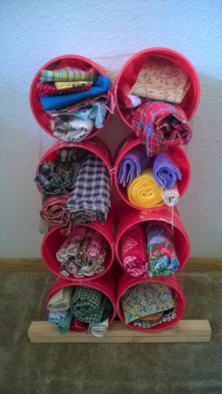 Using Coffee Tubs for Fabric Storage - stack of cans filled with fabric with a short piece of wood under the bottom row to give back tilt