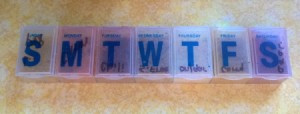 A weekly pill keeper with letters for the days of the week.