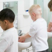 Children washing their hands in a school bathroom.