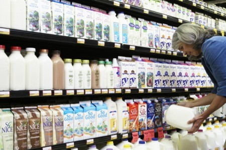 A woman shopping in the milk aisle at a grocery store.