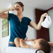 A mother holding a smelly diaper while her baby is on a changing table.