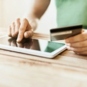 A man using a tablet to pay bills with a credit card.