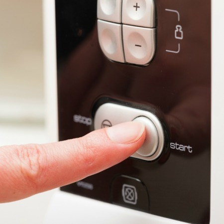 A finger pushing a start button on a microwave.
