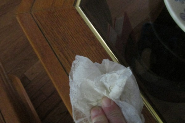 Wiping a table with a dryer sheet used for cleaning.