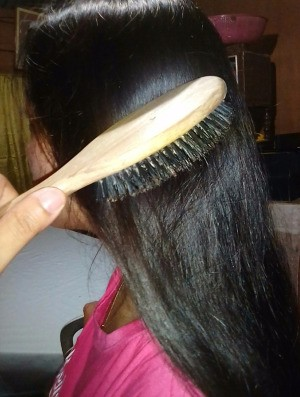 A woman brushing her long brown hair.