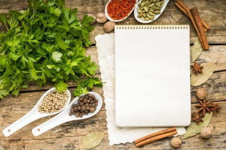 A notebook with spices on a wooden cutting board.