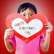 A boy holding a heart shaped Valentine card.