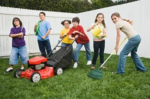 A group of tween aged kids doing yard work.