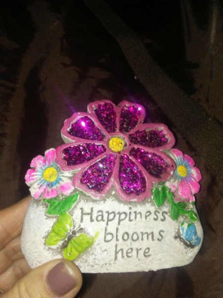 "A flower sign that says ""Happiness blooms here"""